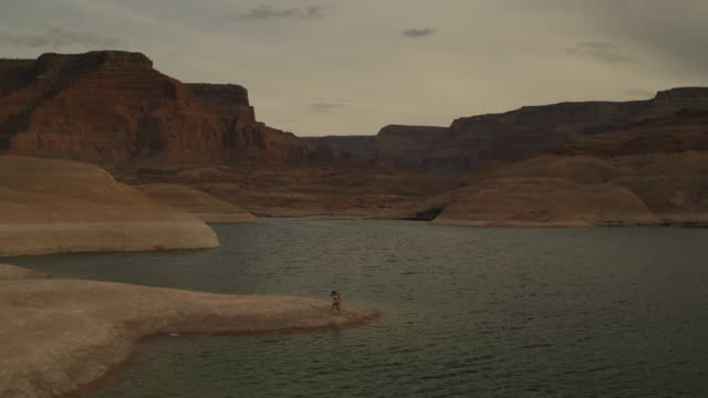 Wide flyover view of passing women on shore of lake near mountains / Lake Powell, Utah, United States