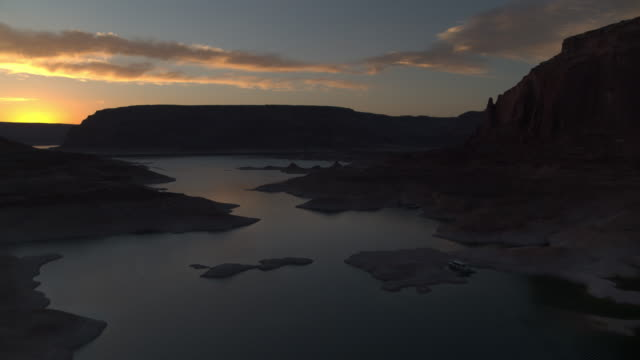 wide flyover view of remote lake near rock formations at sunset / lake powell, utah, united states - lake powell stock-videos und b-roll-filmmaterial