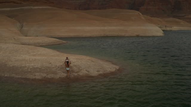 wide flyover view of women exiting lake and sitting on shore / lake powell, utah, united states - lago powell video stock e b–roll