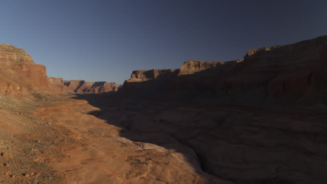 Wide flyover zoom in view of shadows on remote rock formations / Lake Powell, Utah, United States