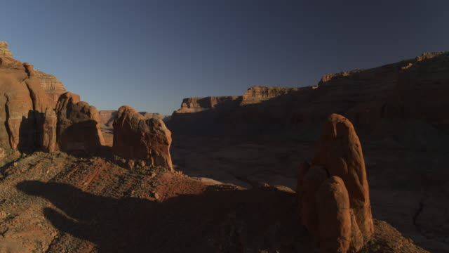wide flyover zoom in view of shadows on remote rock formations / lake powell, utah, united states - rock stock videos & royalty-free footage