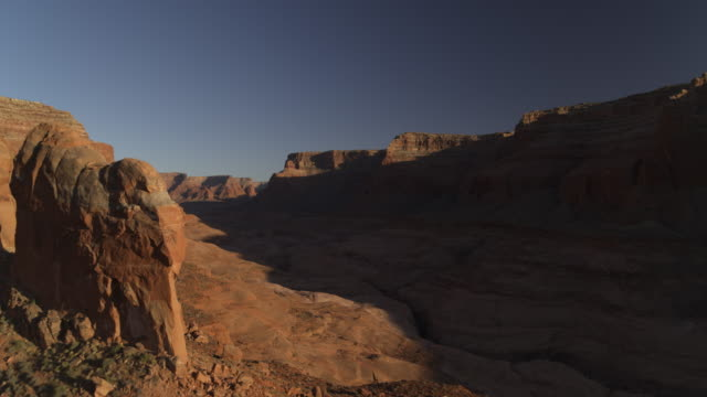 Wide flyover zoom out view of shadows on remote rock formations / Lake Powell, Utah, United States