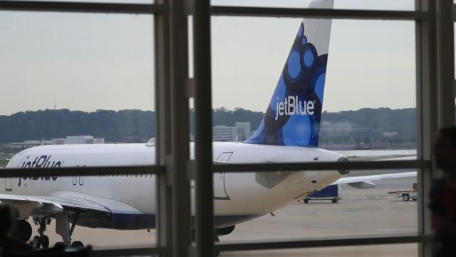 vidéos et rushes de wide footage of a jetblue aircraft idling in the terminal viewed from inside at ronald reagan national airport in washington dc us on friday sept 22... - aéroport ronald reagan
