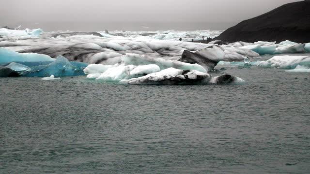 stockvideo's en b-roll-footage met wide: glaciers moving in the sea of diamond beach - arctis