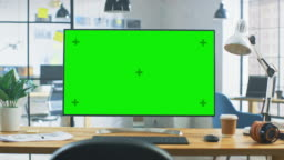 Wide Green Mock-up Screen Desktop Computer Standing on the Desk in the Modern Creative Office. In the Background Bright Creative Loft for Developers and Designers where Professional Working
