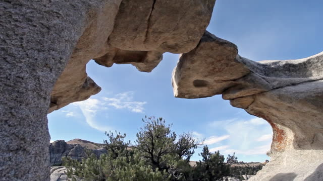 wide hand held shot of window rock arch made out of granite rock. - granite rock stock videos & royalty-free footage
