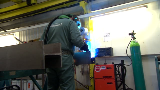wide, handheld shot of a welder working on a steel girder producing blue sparks - engineering stock videos & royalty-free footage