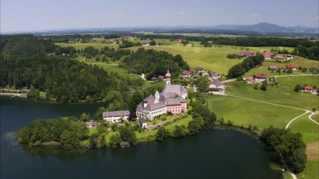 vídeos de stock, filmes e b-roll de wide high angle aerial shot of abbey of remote abbey / anger, berchtesgadener land, germany - alta baviera
