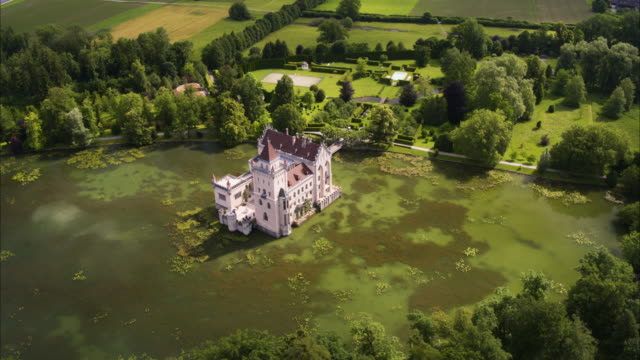 wide high angle aerial shot of castle in remote pond / anif, salzburg-umgebung district, austria - schlossgebäude stock-videos und b-roll-filmmaterial