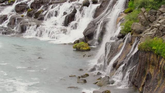 wide high angle crane shot of waterfalls pouring into river / hraunfossar, iceland - crane shot stock videos & royalty-free footage