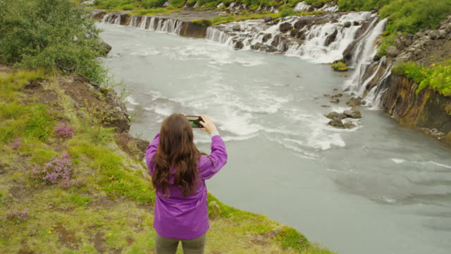 wide high angle crane shot of woman photographing waterfalls / iceland - crane shot stock videos & royalty-free footage