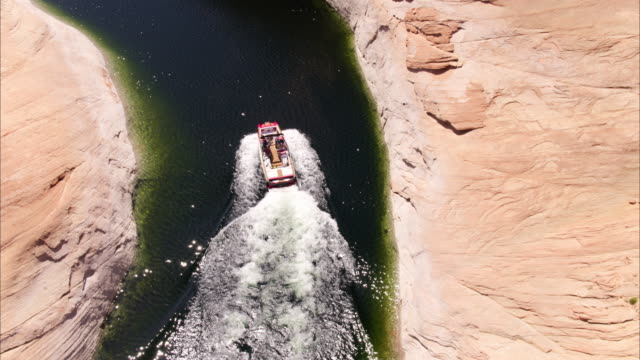 wide high angle flyover tracking shot of speedboat in river / lake powell, utah, united states - lake powell stock videos & royalty-free footage