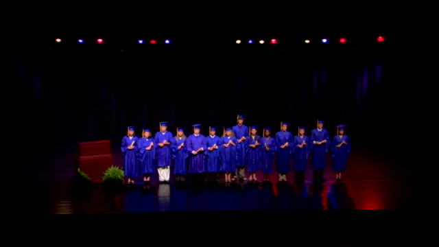 stockvideo's en b-roll-footage met wide high angle of a class of seniors standing on the stage for portraits after graduation. - afstudeer toga
