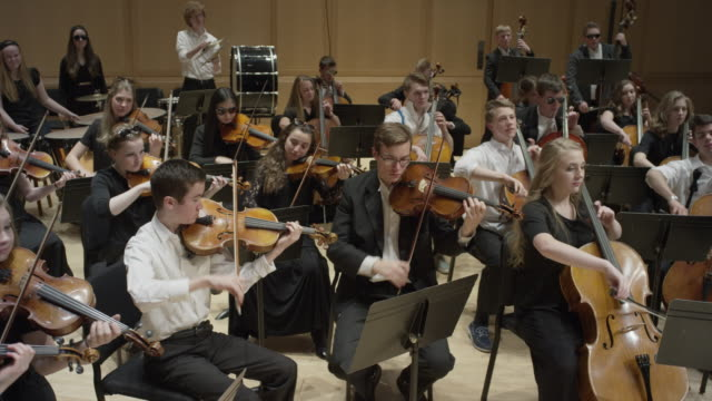 wide high angle panning shot of high school orchestra performing on stage / salt lake city, utah, united states - orchester stock-videos und b-roll-filmmaterial
