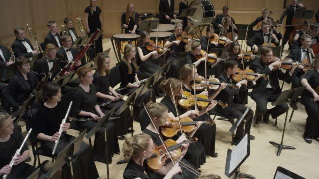 wide high angle panning shot of high school orchestra performing on stage / salt lake city, utah, united states - オーケストラ点の映像素材/bロール