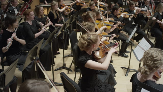 wide high angle panning shot of high school orchestra performing on stage / salt lake city, utah, united states - 交響楽団点の映像素材/bロール