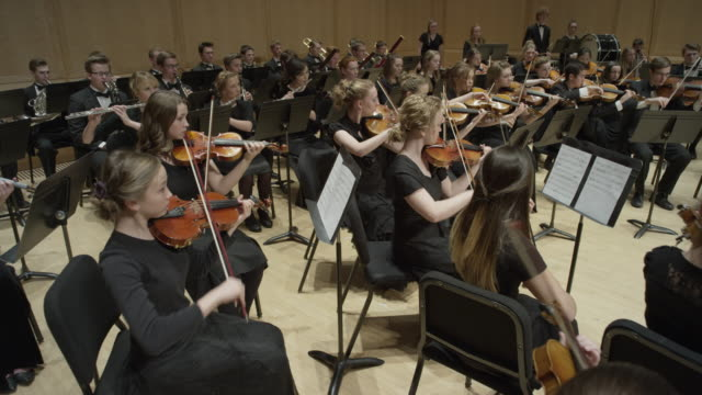 vídeos de stock, filmes e b-roll de wide high angle panning shot of high school orchestra performing on stage / salt lake city, utah, united states - baixo posição