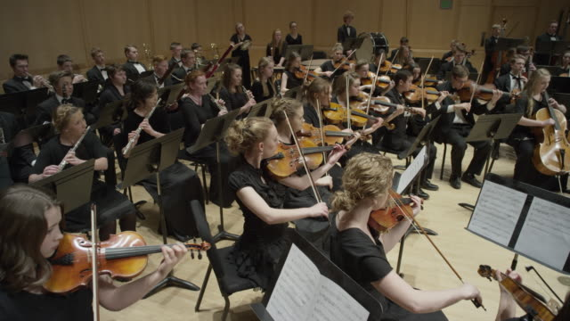 wide high angle panning shot of high school orchestra performing on stage / salt lake city, utah, united states - teenage girls stock videos & royalty-free footage