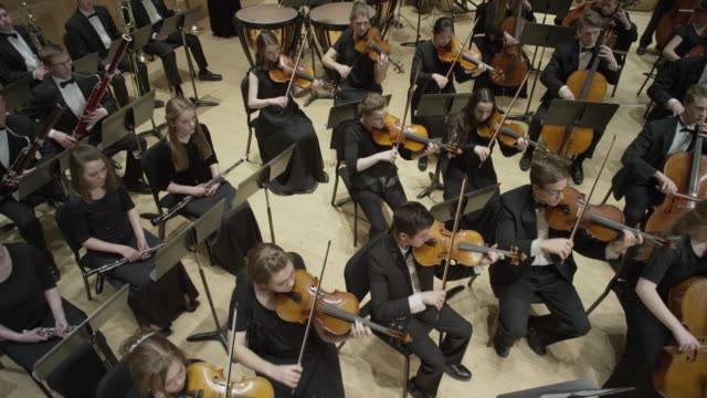 wide high angle panning shot of high school orchestra performing on stage / salt lake city, utah, united states - orchestra stock videos & royalty-free footage