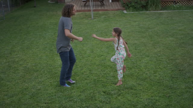 vídeos de stock e filmes b-roll de wide high angle shot of father and daughter dancing in backyard / orem, utah, united states - orem