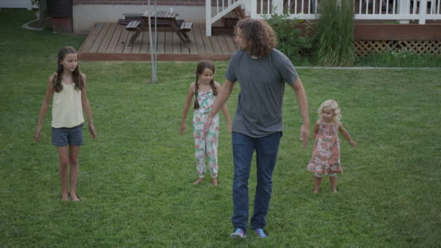 wide high angle shot of father and daughters dancing in backyard / orem, utah, united states - orem utah stock videos & royalty-free footage