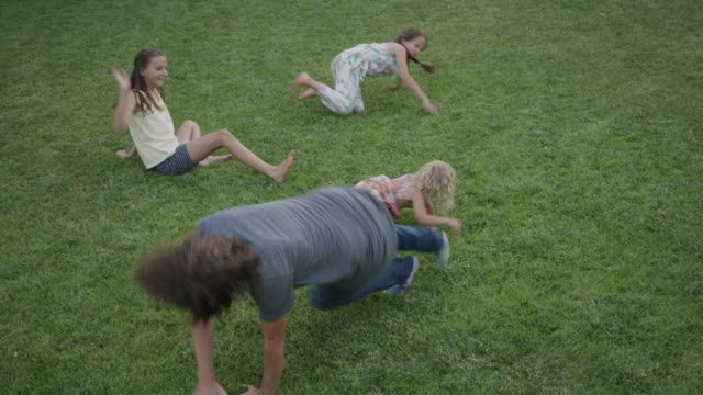 wide high angle shot of father and daughters rolling on lawn / orem, utah, united states - family with three children stock videos & royalty-free footage