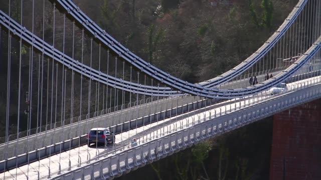 wide high angle shot of vehicles crossing the iconic clifton suspension bridge in bristol uk. no audio - suspension bridge stock videos & royalty-free footage