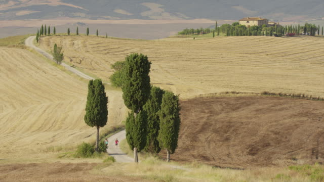 Wide high angle shot of women running on winding rural road / Pienza, Tuscany, Italy
