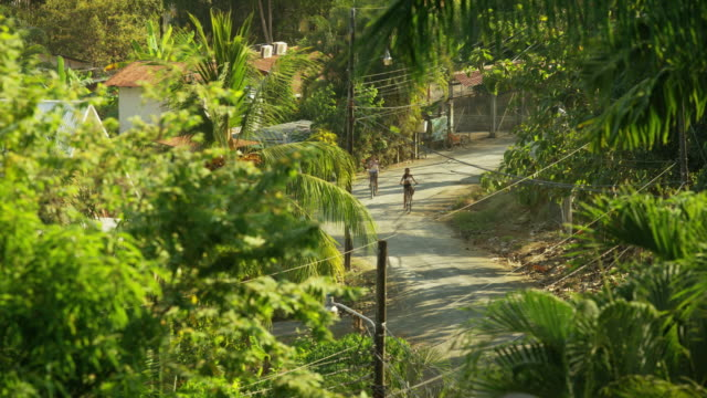 wide high angle slow motion shot of children riding bicycles on road / esterillos, puntarenas, costa rica - puntarenas stock-videos und b-roll-filmmaterial