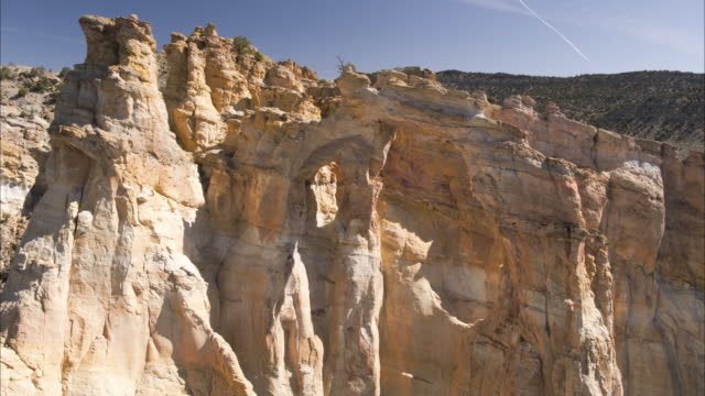 Wide high angle to low angle shot of arch rock formation / Grand Staircase Escalante National Monument, Utah, United States