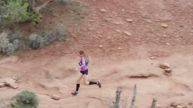 vídeos de stock, filmes e b-roll de wide high angle tracking shot of woman trail running in desert / fisher towers, utah, united states - calções de corrida