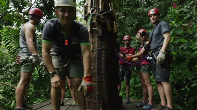 wide high angle tracking shot of zipline in rain forest trees / quepos, puntarenas, costa rica - zip line stock videos & royalty-free footage