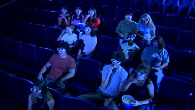 wide high angle view of a group of people watching a 3d movie. - biosalong bildbanksvideor och videomaterial från bakom kulisserna
