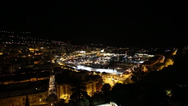 wide high angle view port hercules at night in monaco on tuesday, sept 23 pan l-r and then r-l high angle view illuminated buildings and boats in bay... - exklusiv stock-videos und b-roll-filmmaterial