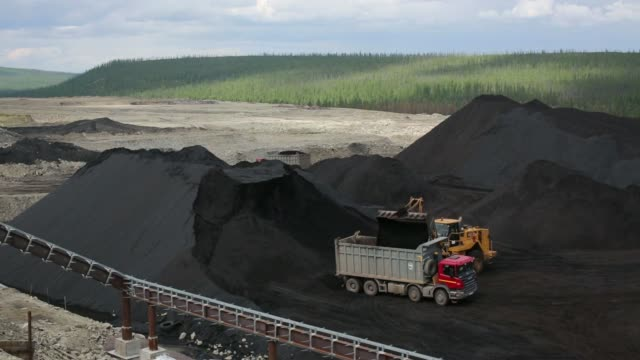 wide high angle view the elga coal complex operated by oao mechel near elga sakha republic russia on thursday june 26 long shot trucks operate in the... - 発電所関係の職業点の映像素材/bロール