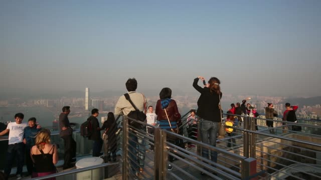 wide high angle view the sun sets over hong kong china on wednesday dec4 tourists take photos at the peak various wide high angle views and pans high... - peak tower stock videos and b-roll footage
