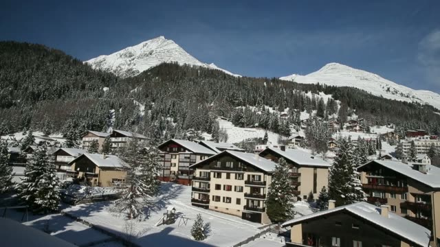 wide high angle views construction cranes rise above a building site and snow covered houses in the town of davos, switzerland, on saturday, jan. 18... - intercontinental hotels group stock videos & royalty-free footage