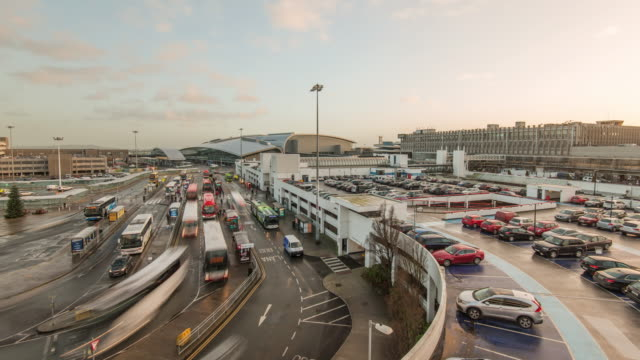 a wide high view of a busy drop off point and short stay parking at dublin's international airport during the christmas holidays - parking stock videos & royalty-free footage