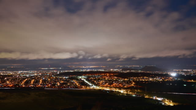 A wide high viewpoint day to night transition of the centre off the city of Edinburgh showing the suburbs King Arthur's seat the city centre and the Firth of Forth in the distance low fast moving clouds are illuminated by the city lights