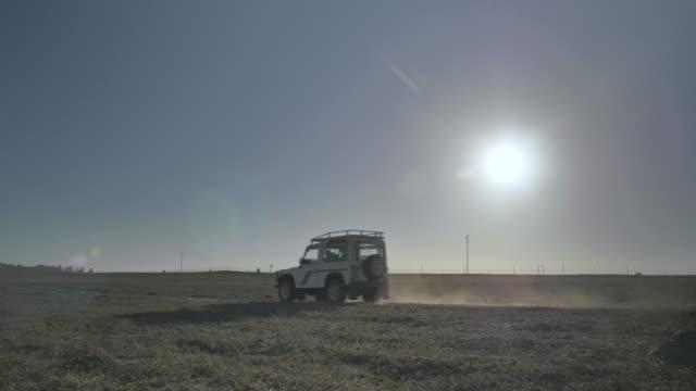 vídeos de stock, filmes e b-roll de wide, land rover drives in open savannah - savana