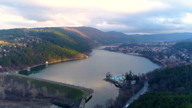 wide landscape shot of a drone flying over a beautiful lake at sunset - bulgaria stock videos & royalty-free footage