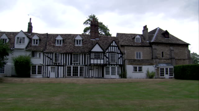 A wide lawn surrounds a Tudor house in Cambridge. Available in HD.