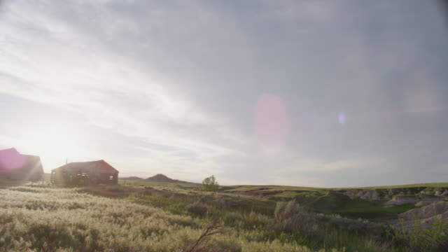 Wide lens - sunsets behind an abandoned, weathered barn and homestead on the high desolate plains.
