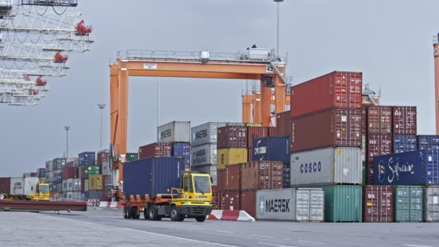 vidéos et rushes de ld trucks conduisant au port conteneur chargé de conteneurs d'expédition - lockdown