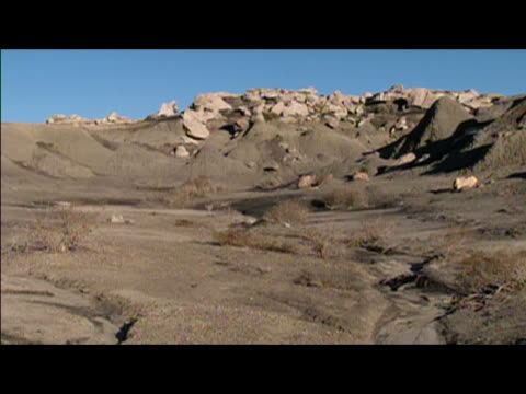 wide locked down shot of arid valley shaped by erosion in badlands of bisti/de-na-zin wilderness area / new mexico - wilderness area stock videos & royalty-free footage