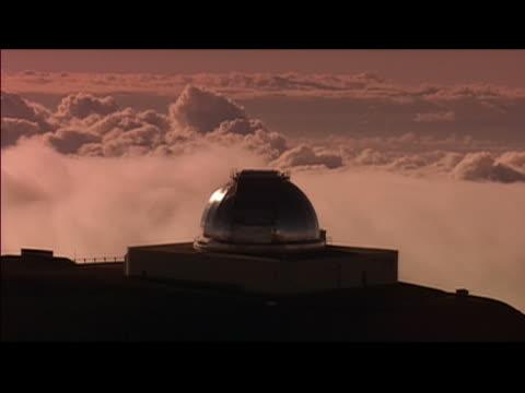wide locked down shot of observatory overlooking clouds from summit of mauna kea / hawaii island, hawaii - breitwandformat stock-videos und b-roll-filmmaterial