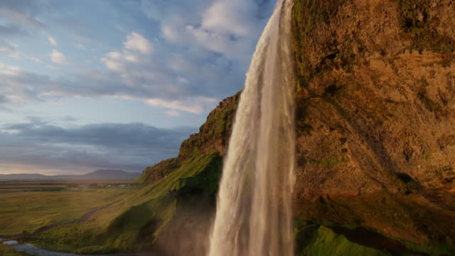 wide low angle crane shot of waterfall pouring over cliff / rangarvallasysla, iceland - low angle view stock videos & royalty-free footage