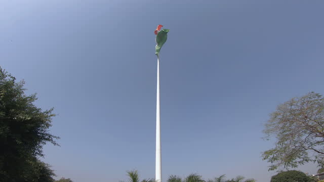 wide, low angle, indian national flag on a white pole, new delhi, india - 旗棒点の映像素材/bロール