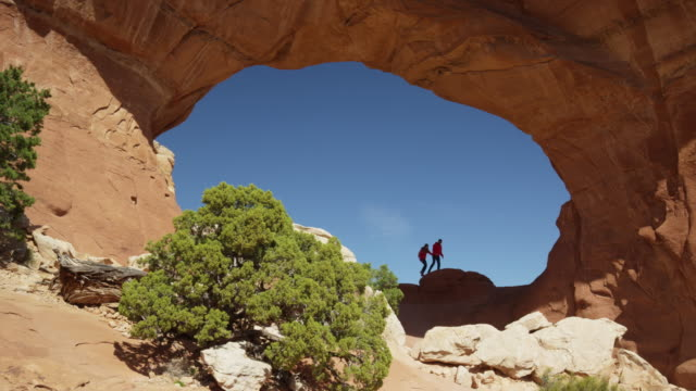 wide low angle panning shot of couple hiking under desert arch / arches national park, utah, united states - western usa stock videos & royalty-free footage