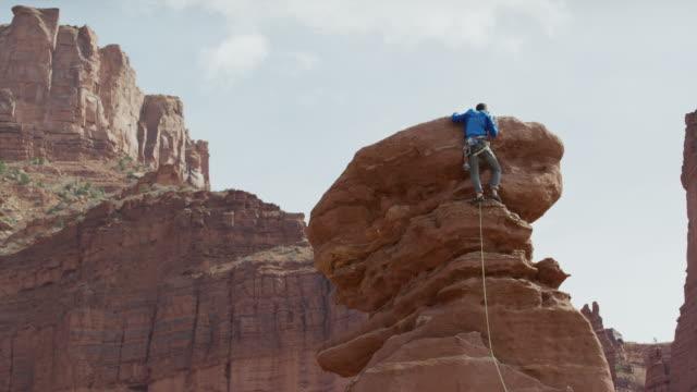 vídeos y material grabado en eventos de stock de wide low angle panning shot of man climbing rock formation / fisher towers, utah, united states - roca